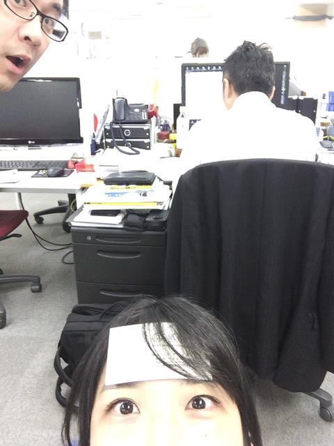 真面目に仕事をしている荒木部長の後ろにてひんやり名刺をおでこに乗せている田中の画像