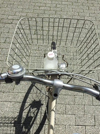 自転車のカゴとPOMジュースのペットボトルに入ったカルピス。