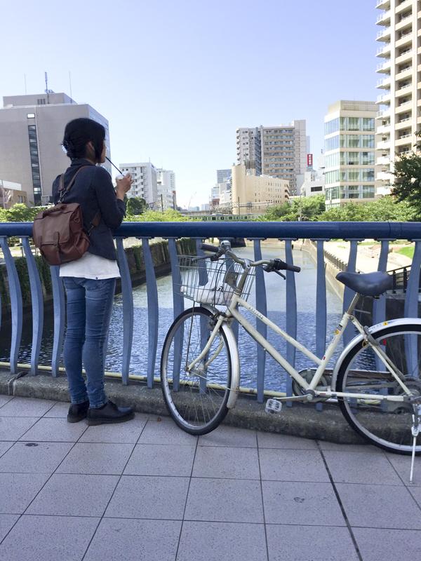 スムージーを飲みながら目黒川を眺める田中